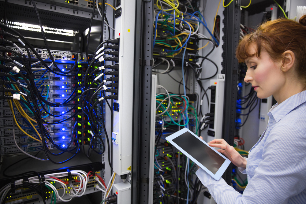 Technician analysing server in large data center