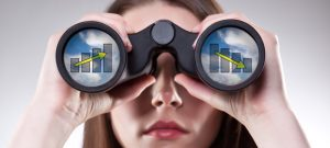 Businesswoman looking through binoculars with vision of profits and losses