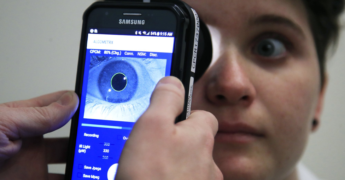 Photo of doctor measuring patient's pupil with special device attached to smart phone