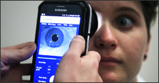 Photo of pain-measuring device being used on eye of woman